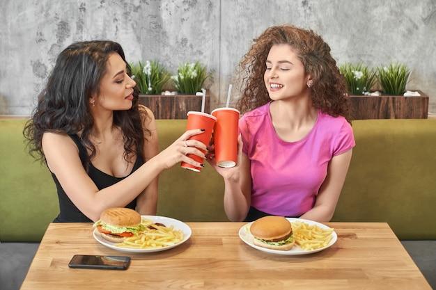 Ładne Dziewczyny Siedzą W Kawiarni I Szczękają Papierowe Kubki. Premium Zdjęcia