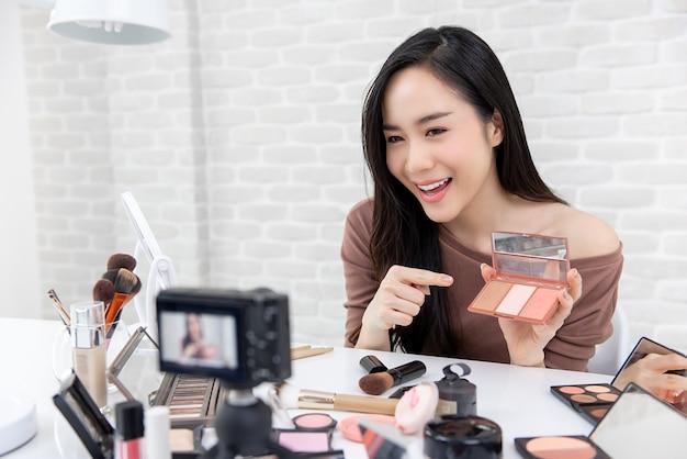 Ładny azjatycki blogger robiący demonstrację wideo o kosmetykach i makijażu. Premium Zdjęcia