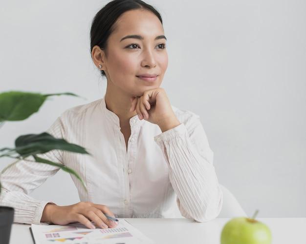 Ładny azjatykci kobiety obsiadanie przy jej biurem Darmowe Zdjęcia