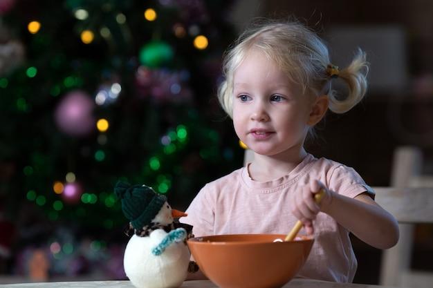 Ładny Blond Maluch Dziewczyna O Niebieskich Oczach Po Posiłku W Otoczeniu Nowego Roku. Choinka Stoi Z Tyłu. Dziewczyna Jest Leworęczna. Premium Zdjęcia