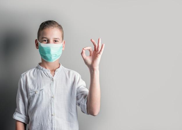 Ładny Chłopak W Białej Koszuli Przedstawiający Znak Ok. Premium Zdjęcia