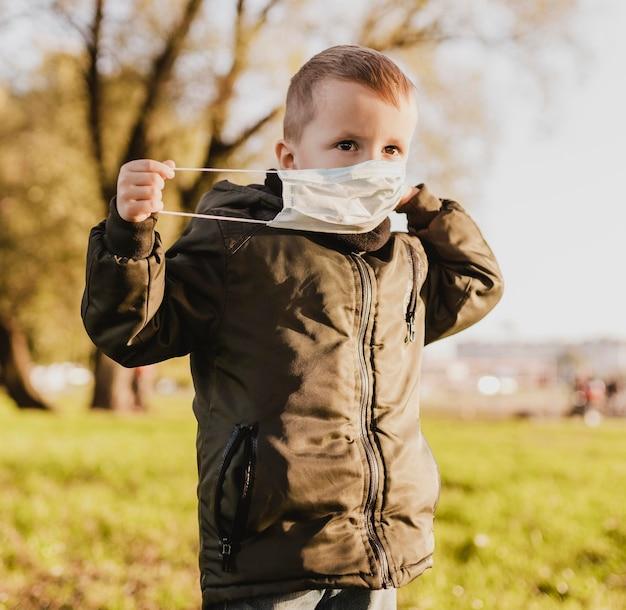 Ładny Chłopiec W Masce Medycznej W Parku Darmowe Zdjęcia