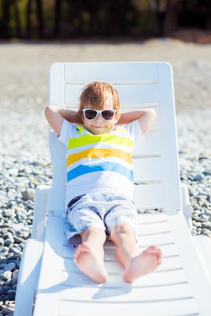 Ładny Mały Blond Chłopiec W Okularach Przeciwsłonecznych Siedzi Na Leżaku Na Wybrzeżu Oceanu Premium Zdjęcia