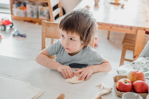 Ładny Mały Chłopiec Przygotowuje Ciasto Do Ciasta W Kuchni Premium Zdjęcia
