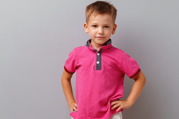 Ładny Mały Chłopiec W Różowej Koszulce Pozowanie Na Szarym Tle Premium Zdjęcia
