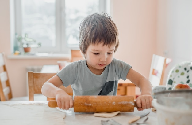 Ładny Mały Chłopiec Za Pomocą Wałka Do Ciasta Do Przygotowania Ciasta Na Ciasteczka W Kuchni Premium Zdjęcia