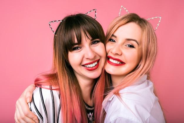 Ładny Pozytywny Portret Szczęśliwej ładnej Najlepszej Przyjaciółki Siostry Kobiet Przytula Uśmiechnięte, Modne Różowe Włosy, Imprezowe Uszy Kota, Rodzinny Wygląd Darmowe Zdjęcia