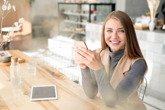Ładny Student Lub Bizneswoman W Elegancki Dorywczo Z Uśmiechem Toothy Podczas Korzystania Z Mobilnych Gadżetów Premium Zdjęcia