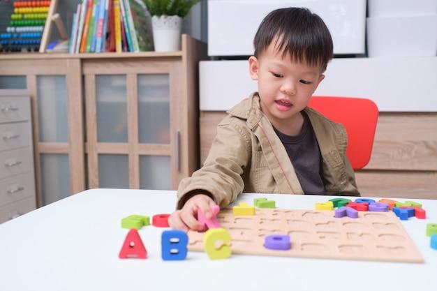 Ładny Uśmiechnięty Chłopiec Przedszkola, Grając Z Bloków Alfabetu, Azjatyckie Dzieci Uczące Się Angielskiego Z Drewnianą Edukacyjną Puzzle Abc Zabawki Premium Zdjęcia