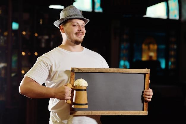Ładny Wesoły Grubas W Bawarskim Kapeluszu, Trzymając Tablicę Lub Talerz Pubu Premium Zdjęcia