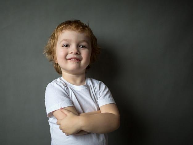 Ładny Wesoły Szczęśliwy Chłopiec Z Kręconymi Włosami Stoi Z Założonymi Rękami Premium Zdjęcia