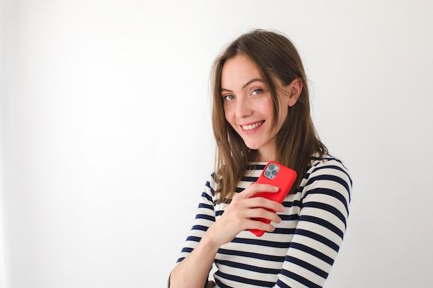 Ładny żeński Czytanie Wiadomości Na Telefon Komórkowy I Patrząc Na Kamery, Stojąc Na Białym Tle Premium Zdjęcia