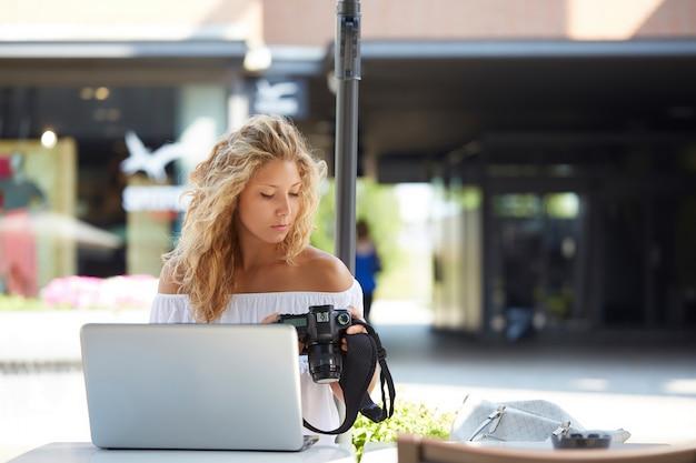Ładny żeński fotograf pracuje z laptopem przy kawiarnią Premium Zdjęcia
