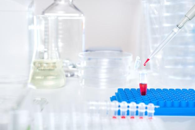 Ładowanie próbki biologicznej do jednorazowej plastikowej tuby do analizy, miejsca na tekst Premium Zdjęcia