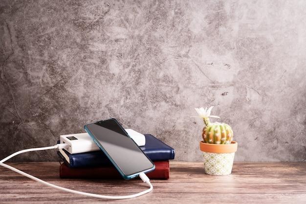 Ładowarka Power Bank Z Smartphone Na Miejscu Pracy Premium Zdjęcia