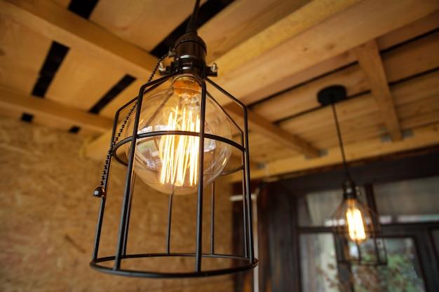 Lampy edisona w metalowym kloszu na otwartej werandzie. Premium Zdjęcia