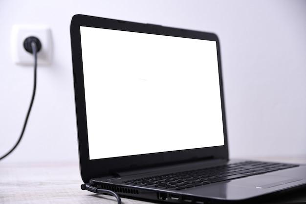 Laptop, Komputer ładuje Się Z Gniazdka 220 V Na Biurku Przy ścianie. Energia, Akumulacja. Makieta Premium Zdjęcia