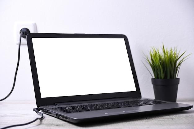 Laptop, Komputer ładuje Się Z Gniazdka O Napięciu 220 V Na Biurku W Pobliżu ściany. Energia, Akumulacja. Makieta Premium Zdjęcia