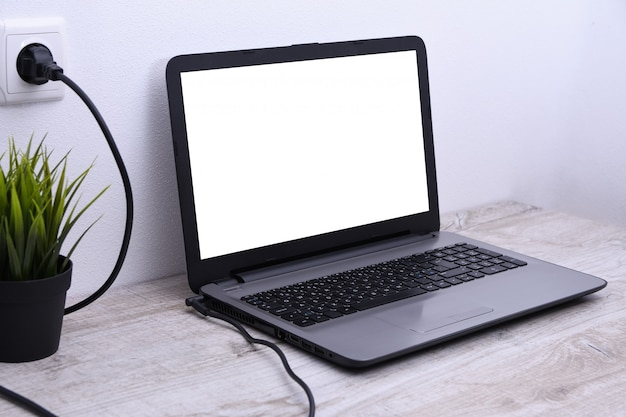 Laptop, Komputer ładuje Się Z Gniazdka O Napięciu 220 V Na Biurku W Pobliżu ściany. Energia, Akumulacja. Premium Zdjęcia