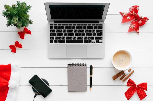 Laptop Na Białym Drewnianym Biurku Otaczającym Czerwonymi Bożenarodzeniowymi Dekoracjami, Odgórny Widok Premium Zdjęcia