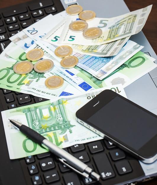 Laptop, Telefon Komórkowy I Gotówka Na Stole Darmowe Zdjęcia