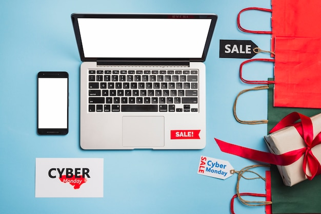 Laptop w pobliżu smartphone, tagi, prezent i pakiety Darmowe Zdjęcia