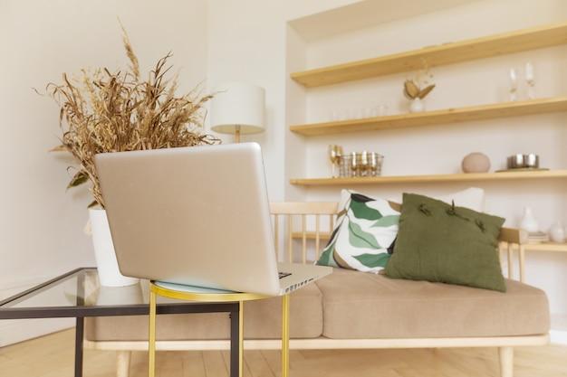 Laptop W Pobliżu Sofy W Salonie Premium Zdjęcia
