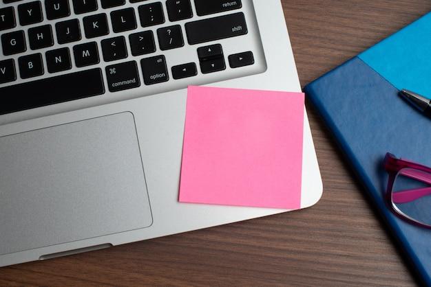 Laptop z różowym nutowym kijem i notatnikiem z czarnym piórem Premium Zdjęcia