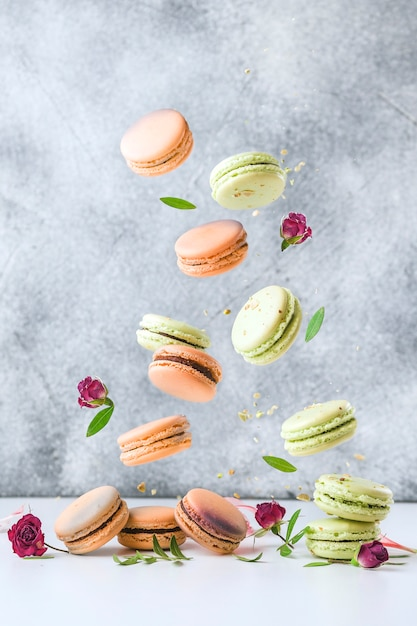 Latające Francuskie Macaroons I Kwiaty Na Szarym Tle. Koncepcja Lewitacji żywności. Premium Zdjęcia