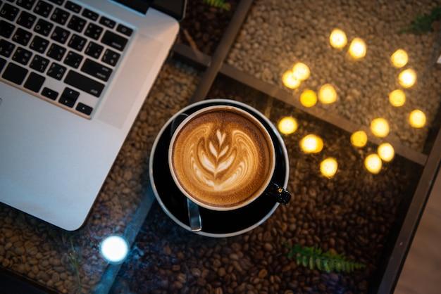 Latte art kawa w czarnej filiżance z laptopem i bokeh świateł na stole, ciemny odcień Premium Zdjęcia