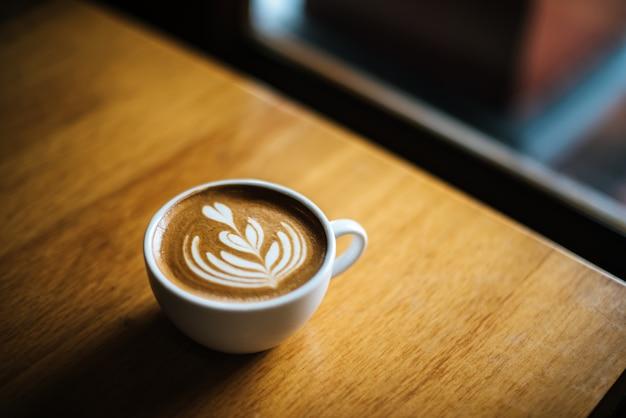 Latte art w filiżance kawy na stoliku kawiarnianym Darmowe Zdjęcia