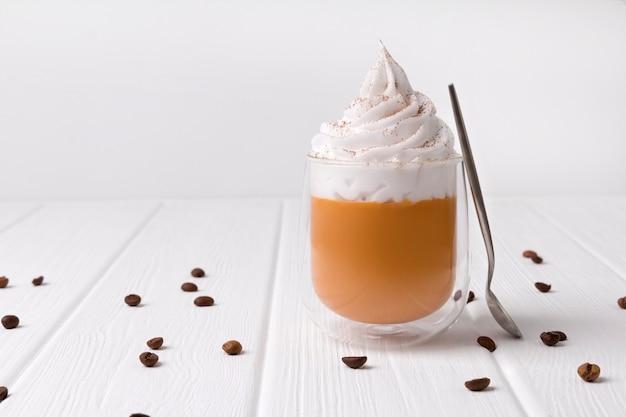 Latte dyniowe z bitą śmietaną i przyprawami na białym drewnianym stole Premium Zdjęcia