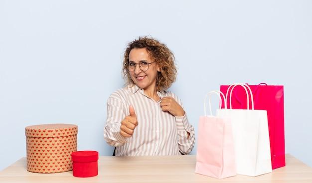 Latynoska Kobieta W średnim Wieku Czująca Się Dumna, Beztroska, Pewna Siebie I Szczęśliwa, Uśmiechająca Się Pozytywnie Z Uniesionymi Kciukami Premium Zdjęcia