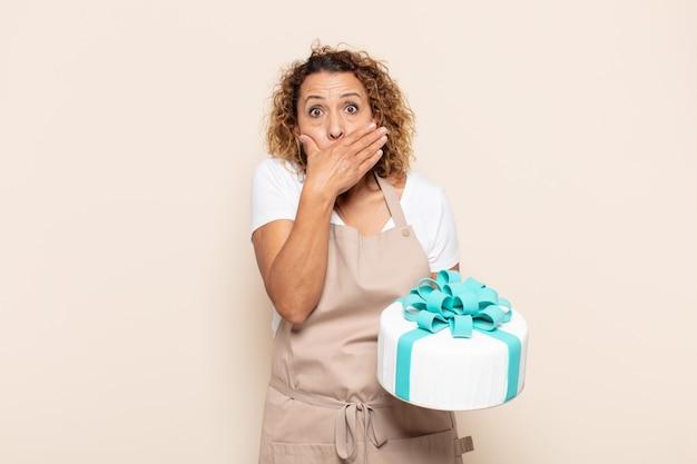"""Latynoska Kobieta W średnim Wieku Zakrywająca Usta Rękami Z Zszokowanym, Zdziwionym Wyrazem Twarzy, Dochowująca Tajemnicy Lub Mówiąca """"ups"""" Premium Zdjęcia"""