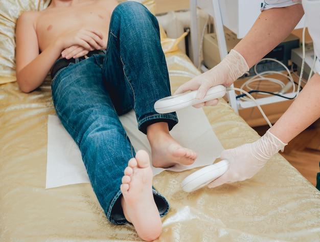 Leczenie I Rozgrzewanie Stóp Młodego Chłopca. Współczesna Pediatria. Premium Zdjęcia