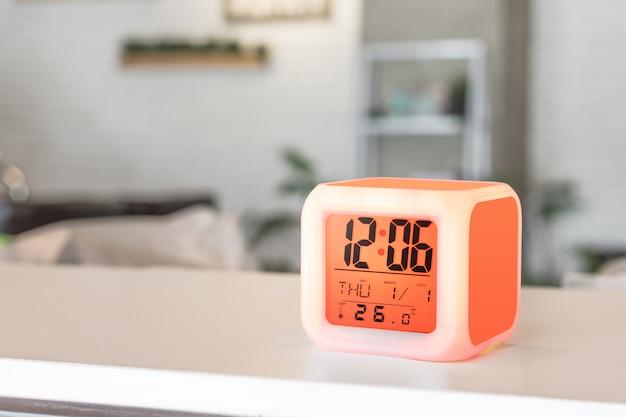 Led budzik stojący na tle tabeli. wyświetlacz timera cyfrowego. Premium Zdjęcia