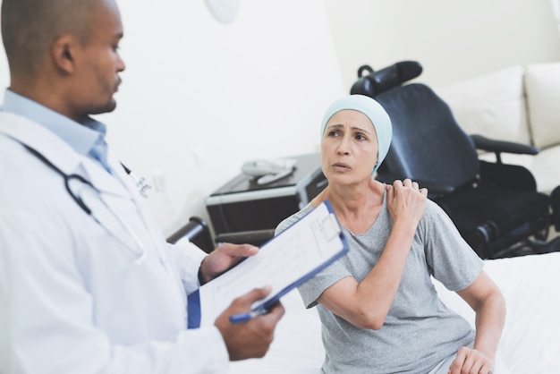 Lek na raka. lekarz odwiedzający starszego pacjenta. Premium Zdjęcia