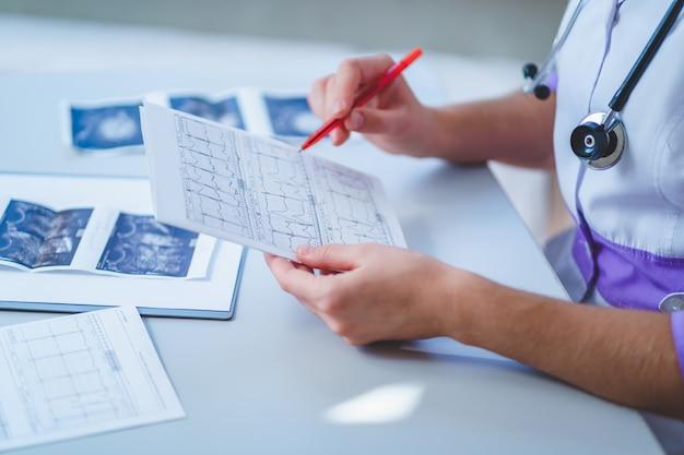 Lekarz Bada Elektrokardiogram Pacjenta Podczas Kontroli Zdrowia I Konsultacji Lekarskiej. Diagnoza I Leczenie Choroby Premium Zdjęcia