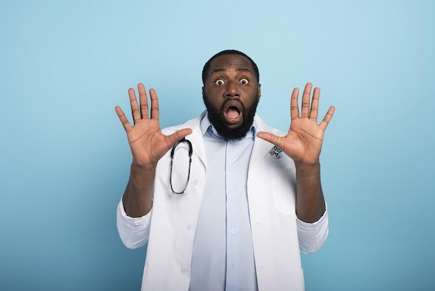 Lekarz Boi Się Ataku Wirusa Codiv19. Niebieska ściana Premium Zdjęcia