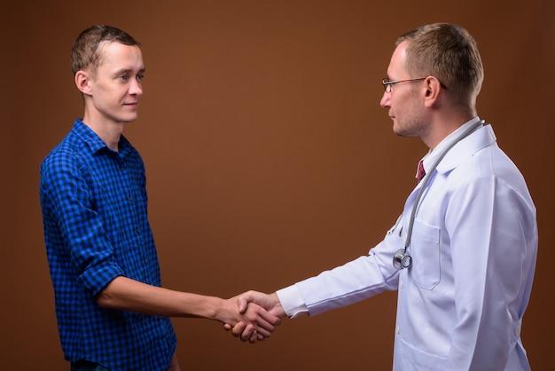 Lekarz Mężczyzna I Pacjent Młody Człowiek Na Brązowym Premium Zdjęcia