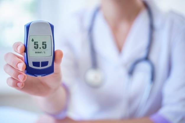 Lekarz Pokazuje Pacjentowi Z Cukrzycą Glukometr Z Poziomem Glukozy We Krwi Podczas Konsultacji Lekarskiej I Badania W Szpitalu. Cukrzycowy Styl życia I Opieka Zdrowotna Premium Zdjęcia