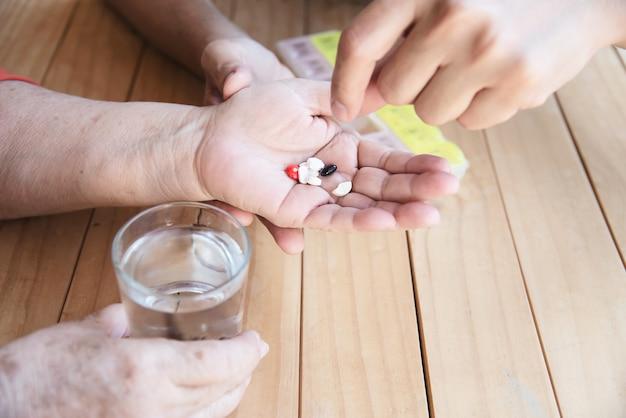 Lekarz pomaga pacjentowi prawidłowo jeść tabletkę leku w pudełku na pigułki Darmowe Zdjęcia