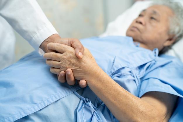 Lekarz Trzymając Się Za Ręce Pacjent Azjatycki Starszy Kobieta Z Miłością. Premium Zdjęcia