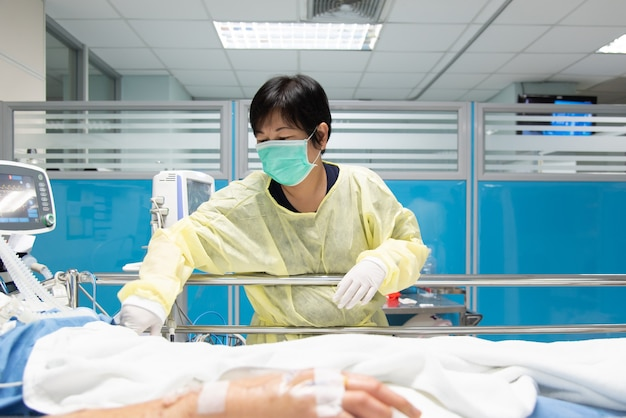 Lekarz Używa Monitora Z Objawami życiowymi Do Opieki Medycznej Nad Wirusem Grypy, Koronawirusem, Cre. Lub Vre. Zakażony Starszy Pacjent Na łóżku Pacjenta Na Oddziale Intensywnej Terapii (oiom). Premium Zdjęcia