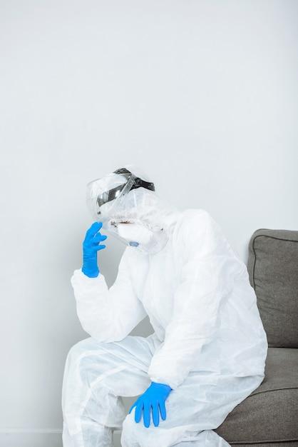 Lekarz W Kombinezonie Ochronnym Ppe Hazmat Jest Zestresowany Podczas Wybuchu Pandemii Koronawirusa Covid-19. Premium Zdjęcia