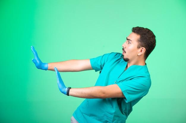 Lekarz W Mundurze I Masce Na Ręce Zapobiegając Sobie. Darmowe Zdjęcia