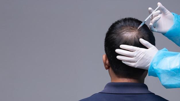 Lekarz wstrzykuje serum witaminowe wypadanie włosów Premium Zdjęcia