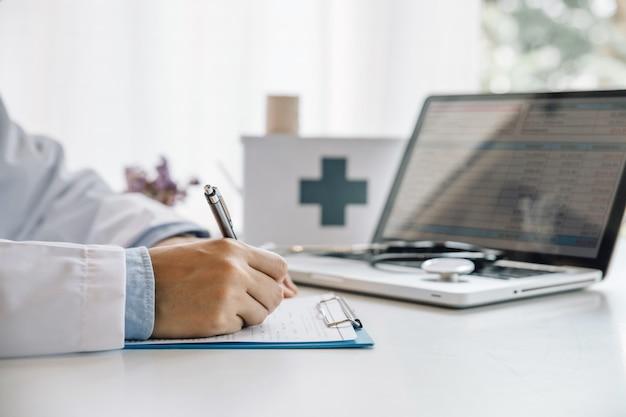 Lekarz Wypełniając Formularz Medyczny Siedząc Przy Biurku W Biurze Szpitala. Lekarz W Pracy. Premium Zdjęcia