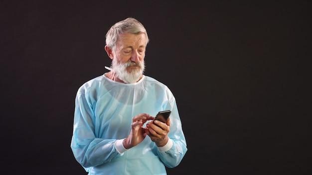 Lekarz Z Siwymi Włosami W Kombinezonie Chirurgicznym Używa Smartfona Na Ciemnej Przestrzeni. Premium Zdjęcia