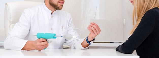 Lekarz Z Urządzeniem Do Usuwania żylaków Wyjaśniający Procedurę Pacjentce. Flebolog Mężczyzna Chirurg Pracuje W Nowoczesnej Klinice. Narzędzia Medyczne W Szpitalu. Leczenie żylaków. Premium Zdjęcia